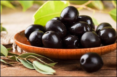 Black-olives-close-up-on-wooden-plate