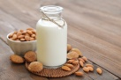 Almond milk in bottle with nuts on wooden background